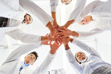 Low Angle View Of Smiling Doctors Stacking Hands While Standing At Hospital