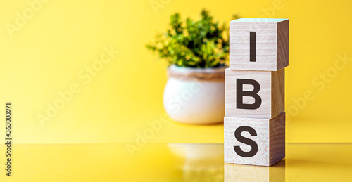 IBS text - Irritable Bowel Syndrome - on wooden cubes, yellow background Canvas-taulu