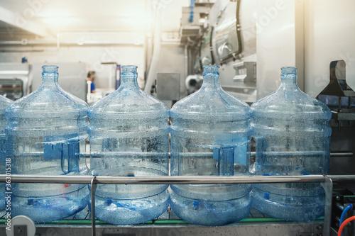 Fototapeta Plastic PET bottles or gallons on production line or conveyor belt in water factory for bottling pure drinking water. obraz