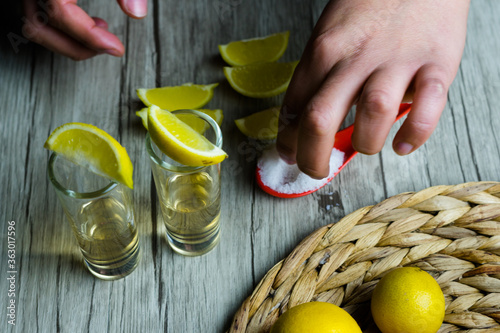 Photo tequila con limón y sal,  sobre mesa de madera