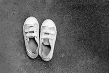 Old White Shoes On Cement Floor.