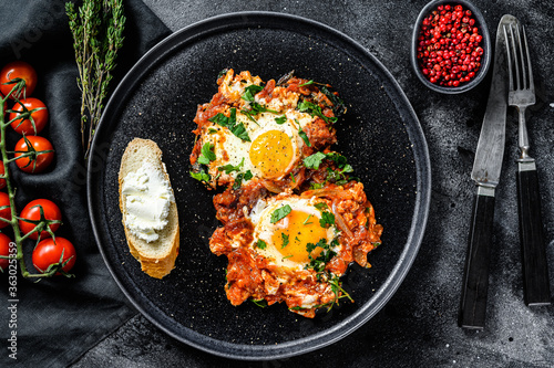 Fototapeta Shakshuka, Scrambled eggs with tomatoes and vegetables. Breakfast in the plate.  Black background. Top view obraz