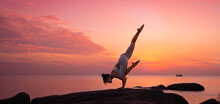 Side View Of Woman Practicing Yoga On Rock By Sea Against Dramatic Sky During Sunset