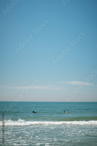 Surfers paddling out to catch a wave off the coast of South Korea