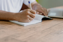 Midsection Of Man Writing In Book By Laptop On Desk