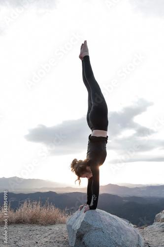 Fototapeta Full Length Side View Of Woman Exercising On Rock Against Sky During Sunset