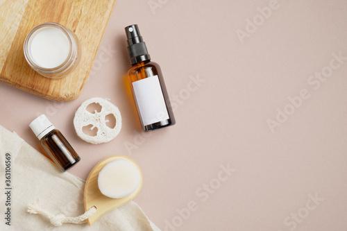 Fototapeta Natural bathroom cosmetics set on beige background. Flat lay amber glass sprayer, essential oil, loofah, body brush and organic moisturizer cream. Top view. obraz