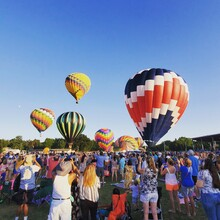 People And Hot Air Balloons Against Sky
