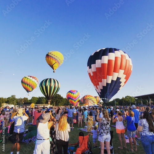 Fotografiet People And Hot Air Balloons Against Sky