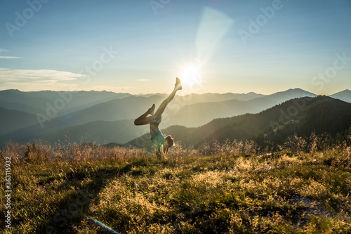 Foto Woman Doing Handstand On Mountain Against Sky During Sunset