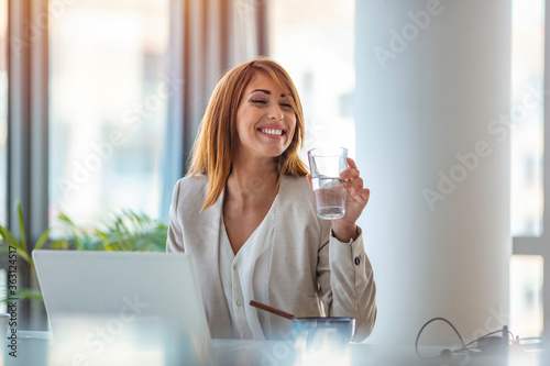 Obraz na płótnie Businesswoman drinking water while working in her office