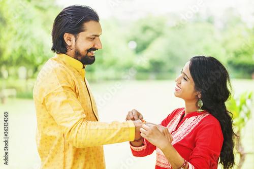 Young indian woman tying rakhi on her brother's hand to celebrate Raksha Bandhan фототапет