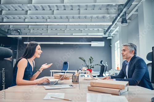 Fotografiet Cheerful man and woman analyzing business data