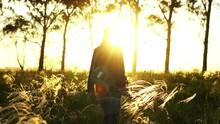 A Man Walks On A Field At Sunset