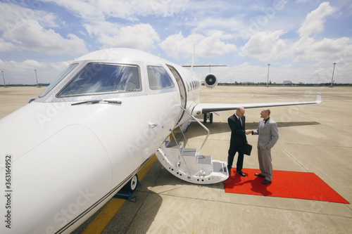 Businessmen shaking hands beside private jet Canvas-taulu