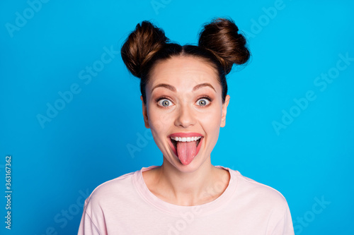 Fototapeta Closeup photo of attractive childish lady two funny buns sticking tongue out mou