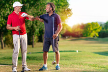 Two Golfers Greet Each Other By Touching Their Elbows