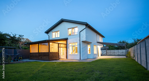 Fototapeta Modern minimalist white color house exterior in the evening with garden, lawn and patio area in summer time obraz