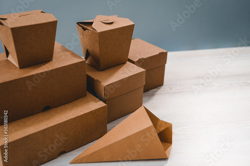 Different types of brown cardboard packaging. For fast food, folding, large and small. The concept of production and design of paper products. Place for text. Selective focus.