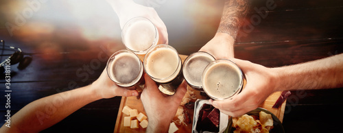 Fototapeta Group of friends toasting with beer in pub, top view. Banner design obraz
