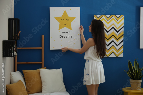 Decorator hanging picture on blue wall. Children's room interior design