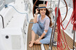 A young girl in a blue striped overalls and a straw hat sits on the deck of a yacht in the azure sea