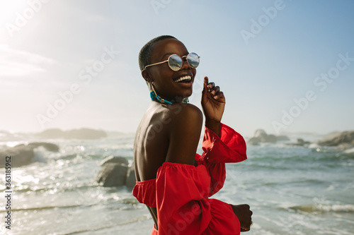 Attractive woman in red dress dancing on the beach