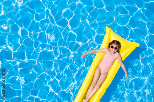 Fototapeta Cute little girl with inflatable mattress in swimming pool, top view. Space for text obraz