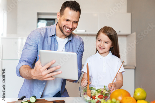 Obraz Cheerful Dad And Daughter Cooking Using Digital Tablet In Kitchen - fototapety do salonu