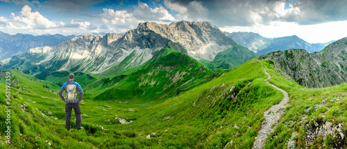 Hiker Man on Hiking Trail with Backpack standing relaxed and enjoying panoramic view to mountains Canvas