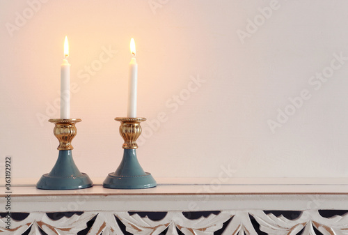 two shabbat candlesticks with burning candles over wooden table Wallpaper Mural