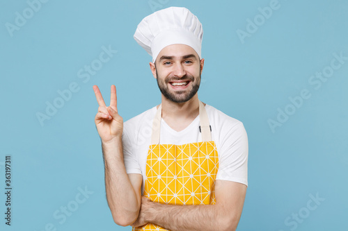 Smiling young bearded male chef or cook baker man in apron white t-shirt toque chefs hat isolated on pastel blue background studio Canvas Print