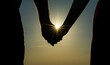 Midsection Of Silhouette Couple Holding Hands Against Sky During Sunset