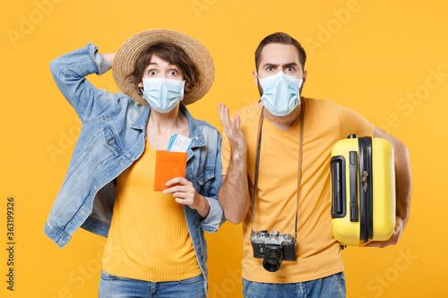 Shocked tourists couple friends guy girl in sterile face mask isolated on yellow background Fototapeta