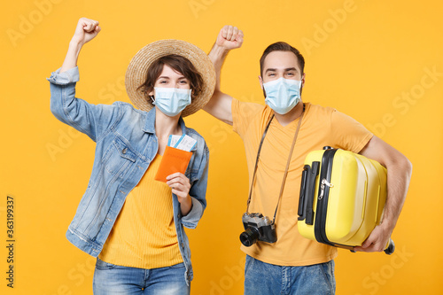 Fototapeta Tourists couple friends guy girl in face mask isolated on yellow background. Epidemic pandemic coronavirus 2019-ncov sars covid-19 flu virus concept. Hold passport tickets suitcase clenching fists. obraz