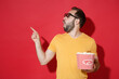 Shocked young man guy in casual yellow t-shirt 3d glasses isolated on red background. People in cinema, lifestyle concept. Watching movie film holding bucket of popcorn pointing index finger aside up.