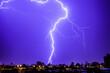 Leinwanddruck Bild - Lightning Over Illuminated Buildings In City At Night