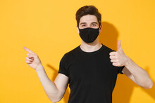 Young Guy In Casual Black T-shirt Face Mask Isolated On Yellow Background Studio. Epidemic Pandemic Coronavirus 2019-ncov Sars Covid-19 Flu Virus Concept. Showing Thumb Up Pointing Index Finger Aside.