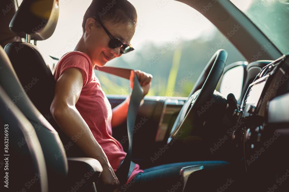 Fototapeta Woman driver buckle up the seat belt before driving car