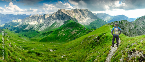 Fotografie, Obraz Hiker Man on Hiking Trail with Backpack standing relaxed and enjoying panoramic view to mountains