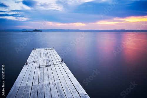 Fotografie, Obraz Wooden Pier On Bolsena Lake At Sunrise Dawn, On Water, Long Exposure And Bientin