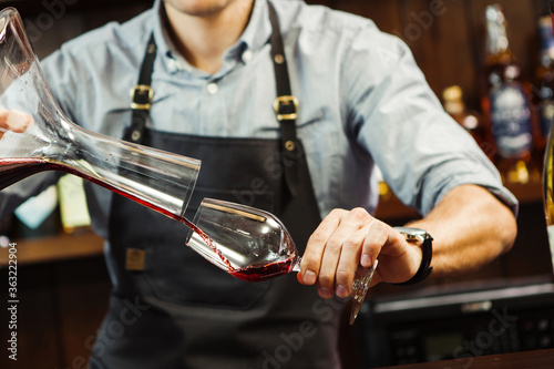 Fototapeta Sommelier pouring wine into glass from mixing bowl. Male waiter obraz