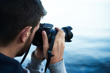 A Young Man Photographer With Digital Dslr Camera Reflex On Shore Lake Or Sea