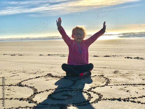 Full Length Of Girl Sitting On Sand At Beach Against Sky Canvas Print