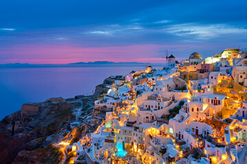Fototapeta Architektura Famous greek iconic selfie spot tourist destination Oia village with traditional white houses and windmills in Santorini island in the evening blue hour, Greece