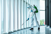 Coronavirus Pandemic. A Disinfector In A Protective Suit And Mask Sprays Disinfectants In Office. Protection Agsinst COVID-19 Disease. Prevention Of Spreding Pneumonia Virus With Surfaces.