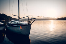 Sailboats Moored In Sea Against Sky During Sunrise