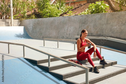 Fototapeta Sport. Woman On Stairs With Bottle Of Protein Shake Having Break. Sporty Girl In Fashion Sportswear Sitting Outdoor Before Intense Cardio Exercising. Outside Fitness Workout As Urban Lifestyle. obraz