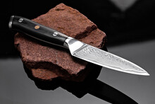 A Large Kitchen Knife With A Black Handle On A Dark Background. Knife With A Wide Sharp Blade. Scratched Steel Surface Of The Knife Blade.