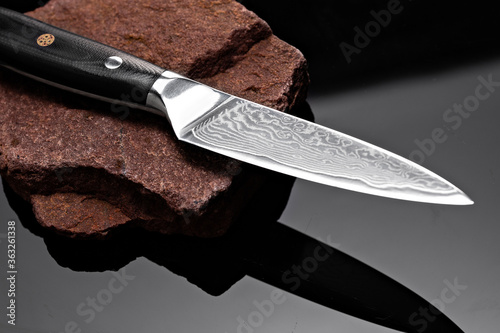 A large kitchen knife with a black handle on a dark background Fototapet